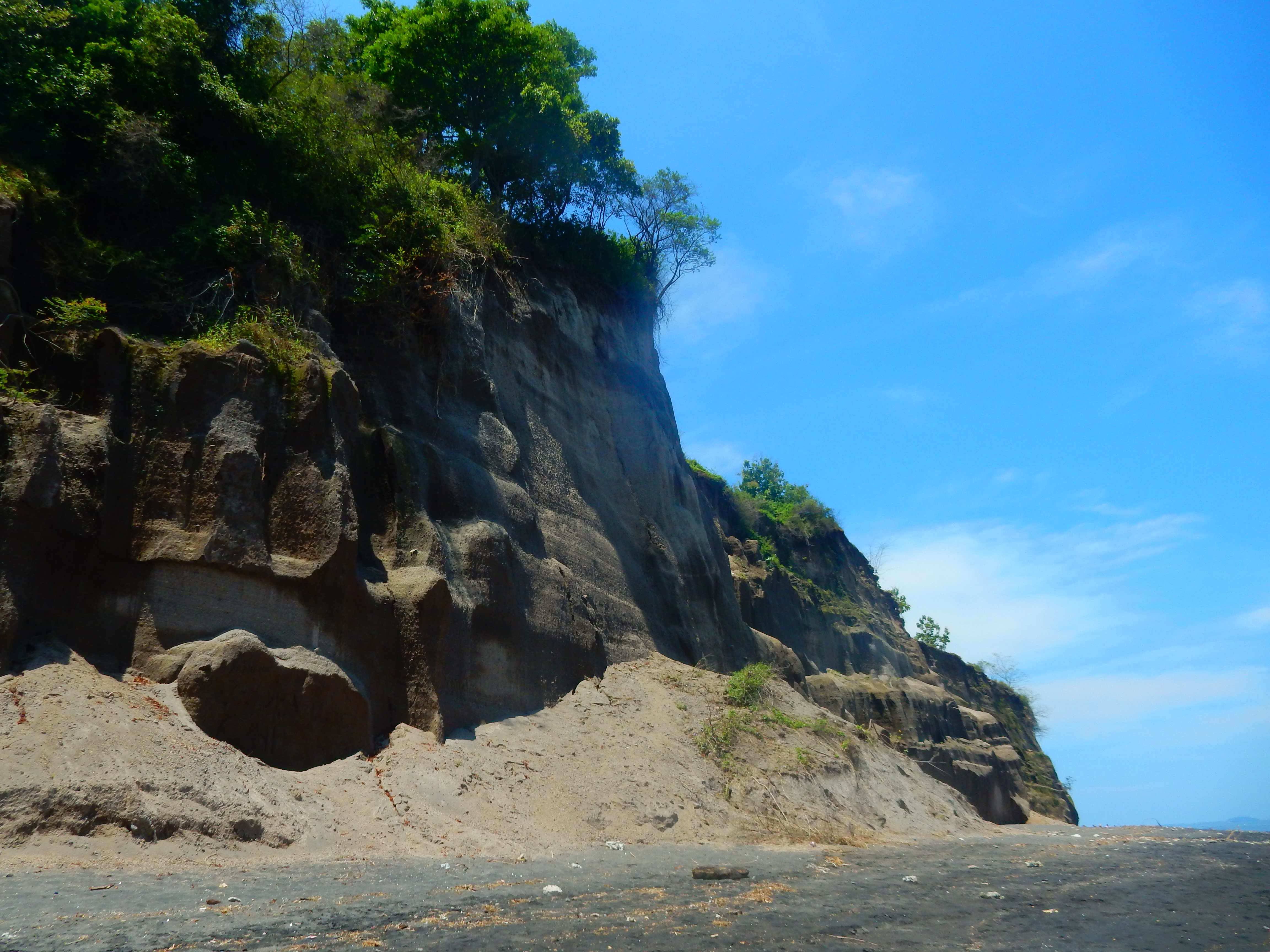 Plage de sable noir, falaises de Pantaî, Lombok, Indonésie.